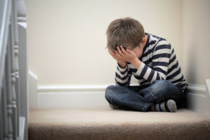 Upset problem child with head in hands sitting on staircase conc